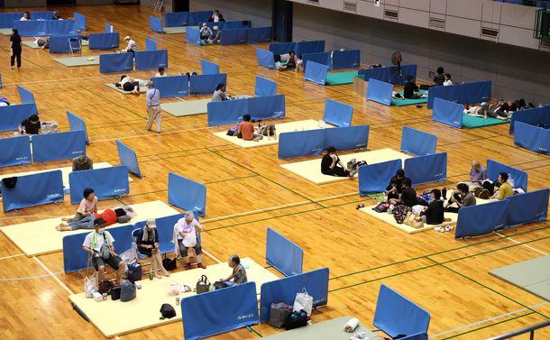 写真・図版 : 熊本県人吉市の避難所。新型コロナウイルス感染防止のため住民同士が距離を約2メートル空けるようにしていた=2020年7月4日