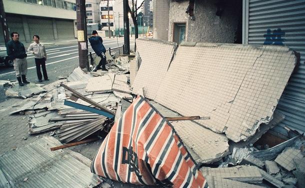 写真・図版 : 阪神・淡路大震災の強い揺れで外壁が歩道に散乱した建物= 1995年1月17日、大阪市西区