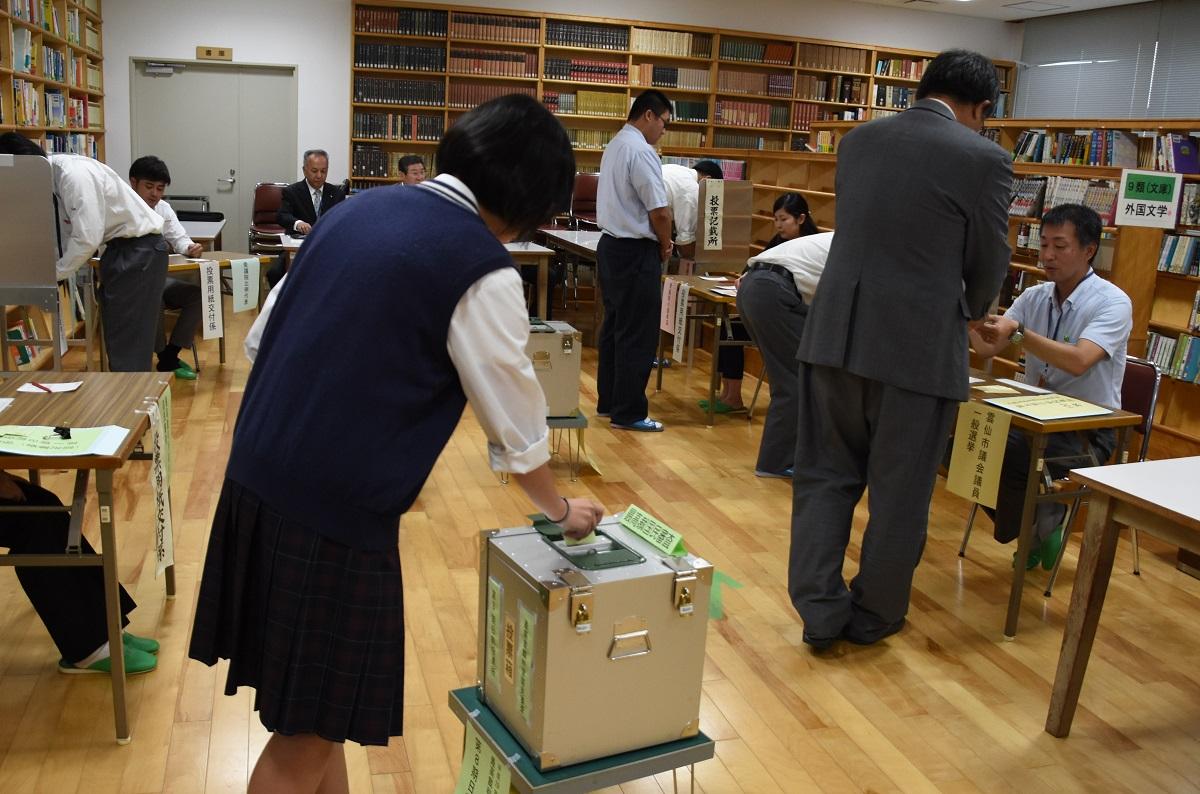 写真・図版 : 校内に設置された期日前投票所で授業時間の合間に投票をする小浜高校の生徒ら=2017年10月16日、雲仙市小浜町