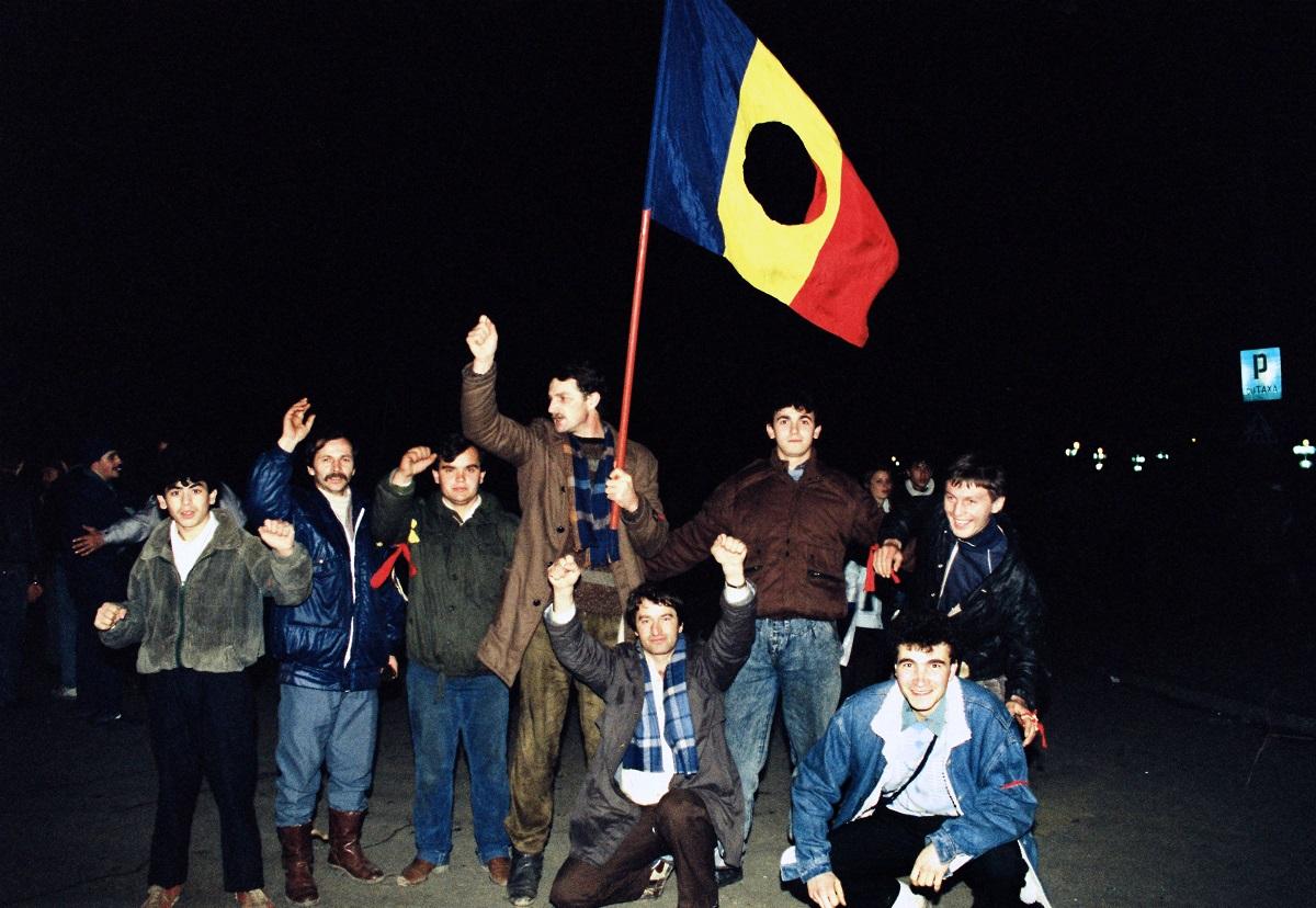 写真・図版 : 真ん中の国章をくり抜いたルーマニア国旗を手に「勝利」と叫ぶ反チャウシェスクのデモ参加者=1989年12月22日、ルーマニア・ティミショアラ