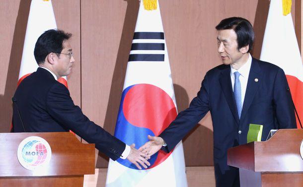 写真・図版 : 2015年12月、慰安婦の日韓政府間合意の後、共同記者発表を終え握手する岸田文雄外相(左)と韓国の尹炳世外相=ソウル・韓国外交部