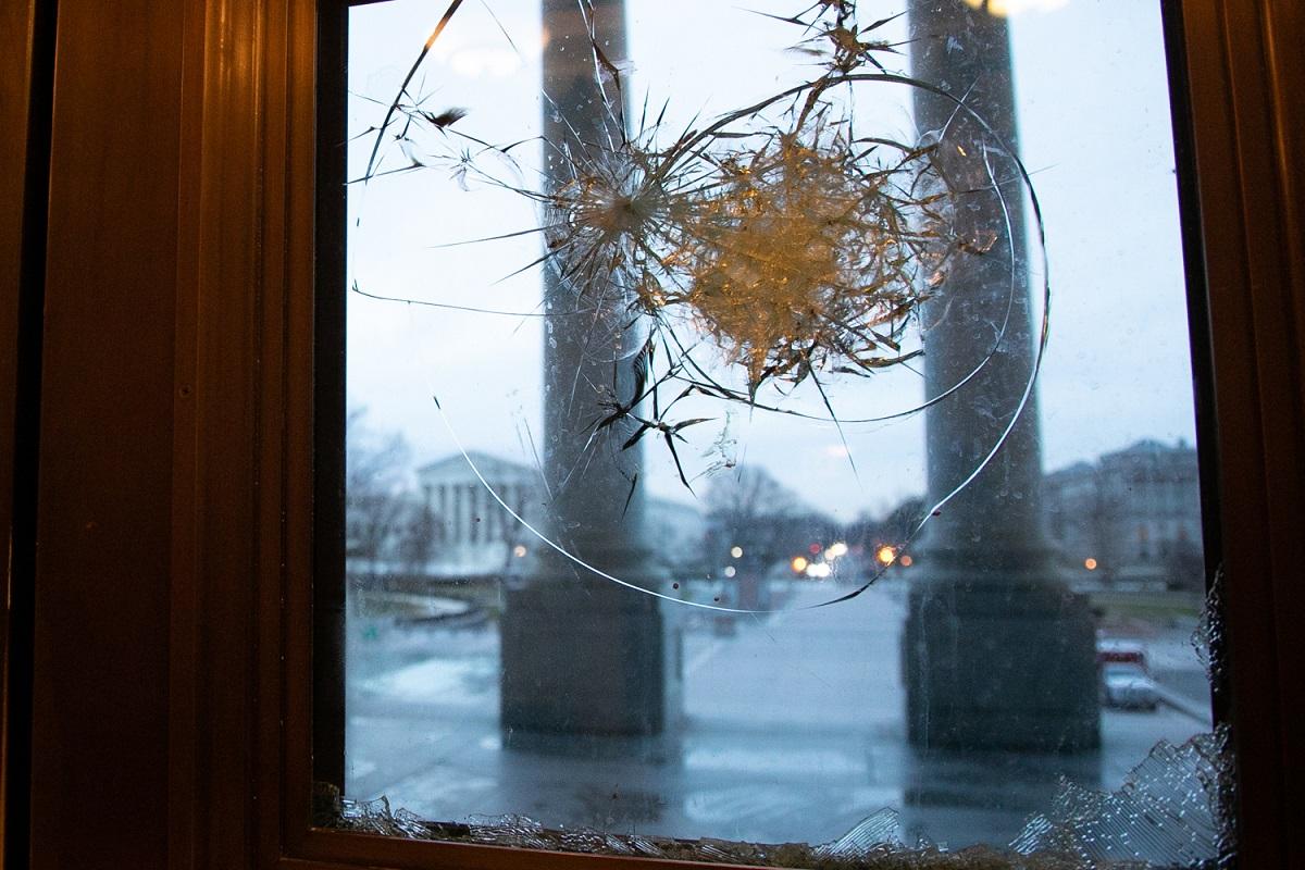 トランプ大統領の支持者たちの乱入事件により割られた、ワシントンの連邦議会議事堂入り口の窓=8日、