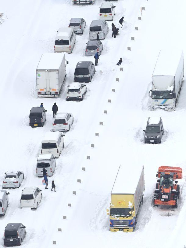 写真・図版 : 車の立ち往生が続き、車道に人影が見える北陸自動車道=2021年1月10日、福井県坂井市周辺