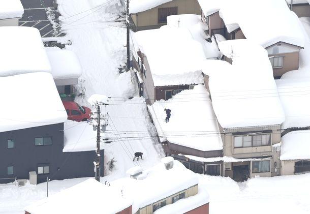 写真・図版 : 富山市の民家の屋根に積もる雪=2021年1月10日