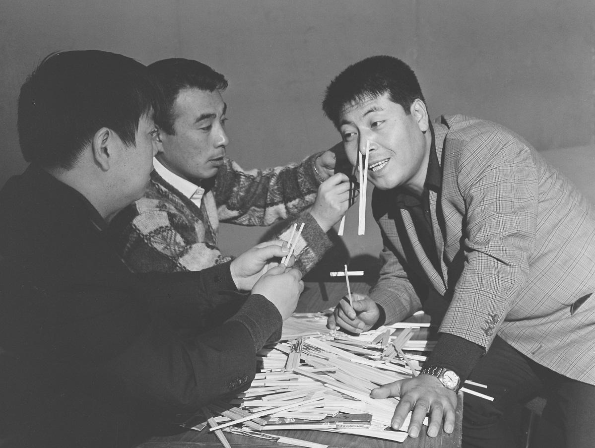 写真・図版 : ワリバシのCMを題材にどうコントを演じるか話し合うクレージーキャッツのハナ肇(右)と植木等と谷啓(左)=1963年12月