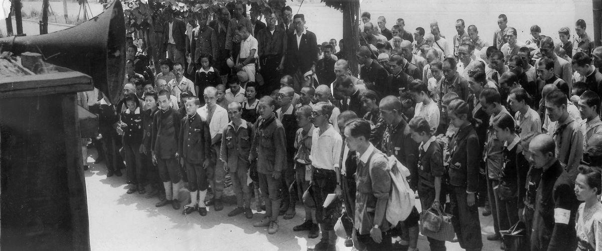 写真・図版 : 終戦を告げる玉音放送に聴き入る人々=1945年8月15日正午すぎ、大阪・梅田の曽根崎警察署前