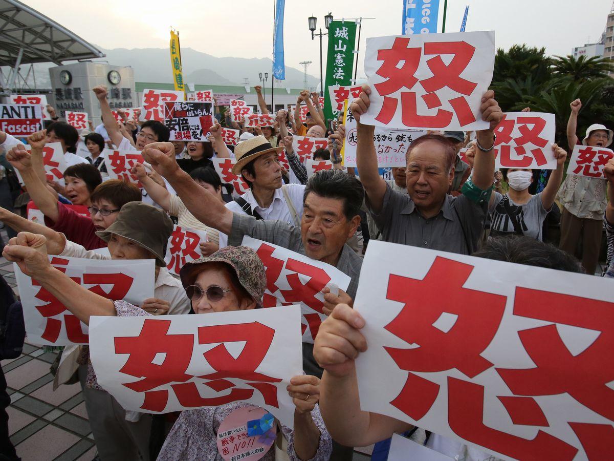 写真・図版 : 集団的自衛権の行使容認に反対する動きは全国で続いた。被爆地・長崎での集会の参加者は「絶対に許さないぞ」と拳を突き上げた=2014年7月1日、JR長崎駅前