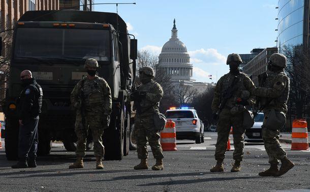 写真・図版 : 米連邦議会議事堂から数百メートル離れた場所で警戒に当たる州兵=2021年1月20日、ワシントン