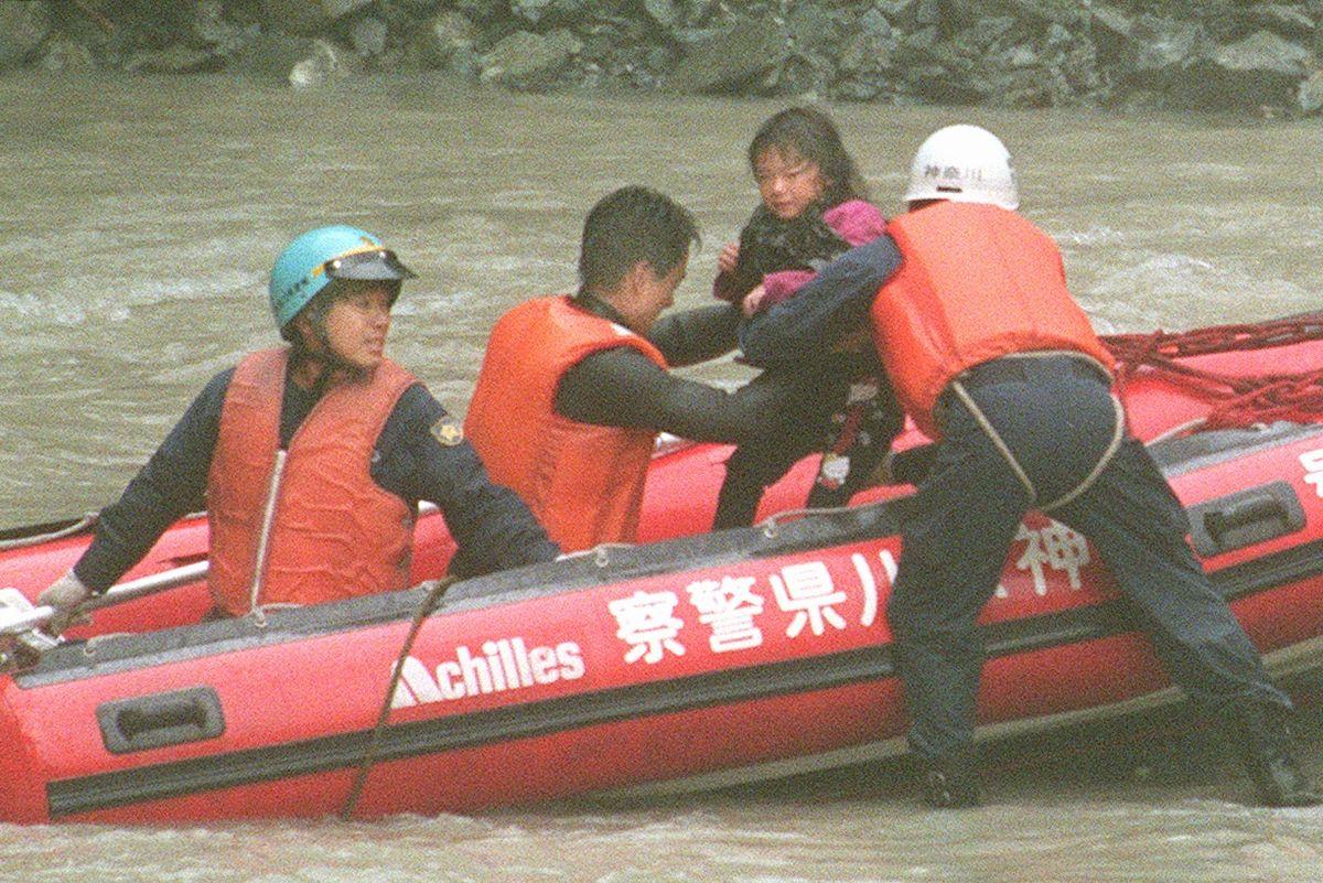 写真・図版 : 玄倉川水難事故で神奈川県警のゴムボートで救出された女の子=1999年8月15日、神奈川県山北町。朝日新聞社