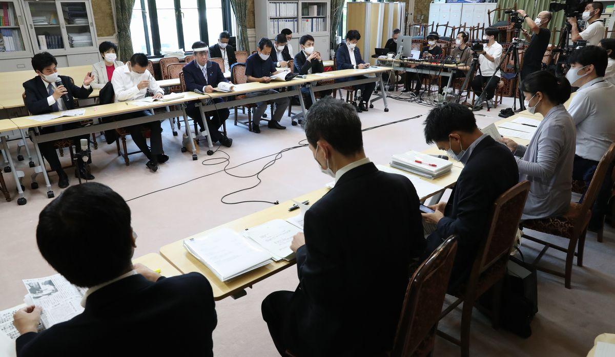 写真・図版 : 政府のコロナ対策に関する野党合同ヒアリングで官僚たち(手前)に質問する議員たち=2020年8月、国会内。朝日新聞社
