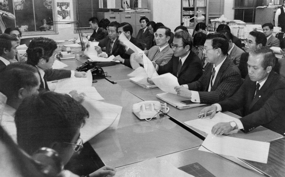 写真・図版 : 1984年度予算折衝で大蔵省側(左)から原案内示を受ける防衛庁側=1983年12月、東京・霞が関。朝日新聞社