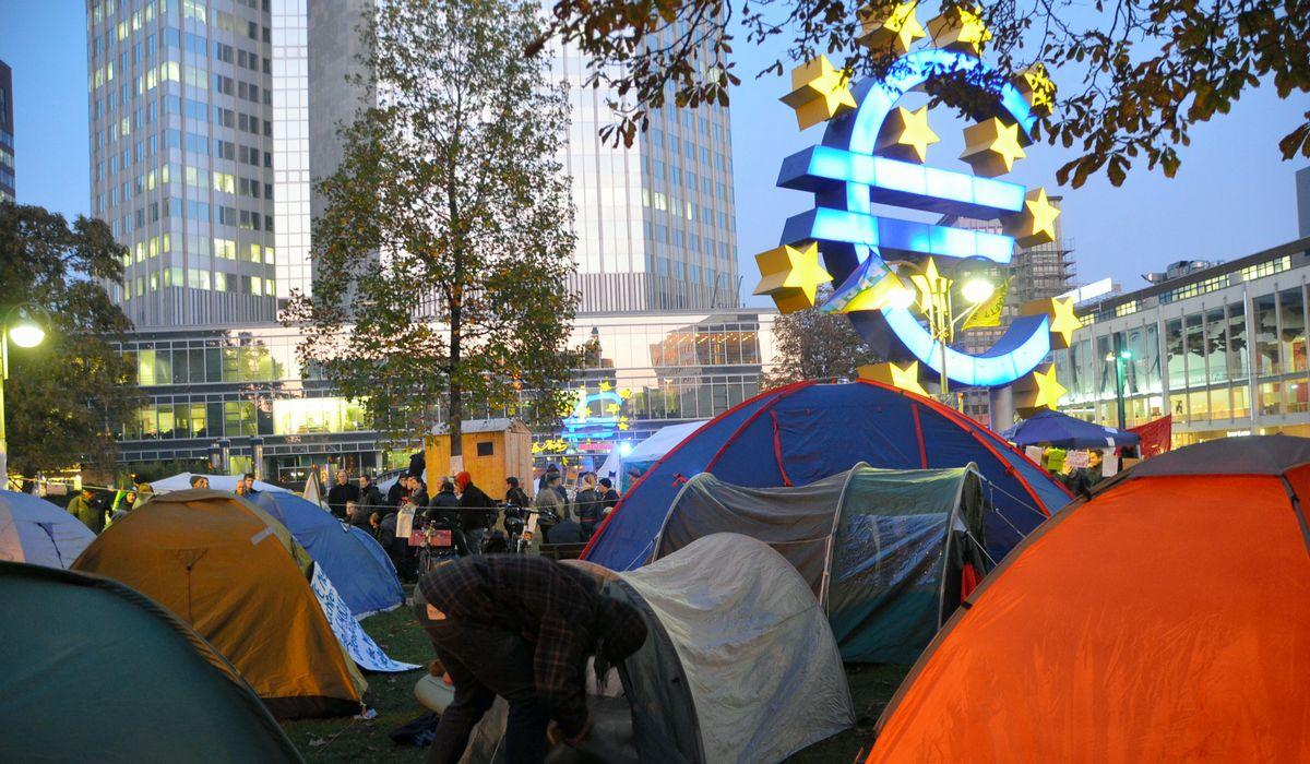写真・図版 : 欧州中央銀行本部前には「反格差」の立場からの抗議を示すためテントを張って泊まり込む人たちも出た=2011年10月22日
