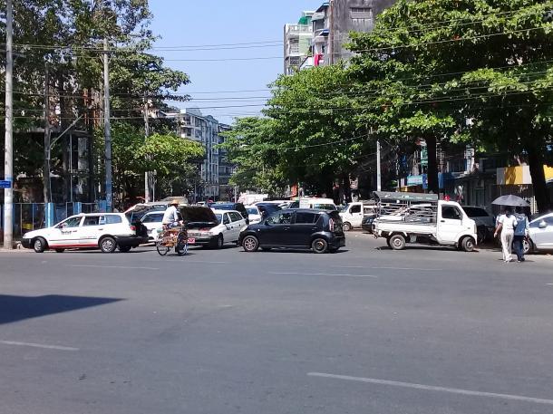 写真・図版 : 20210217_121133 故障と偽って交差点をブロックするデモ隊の車(著者撮影)
