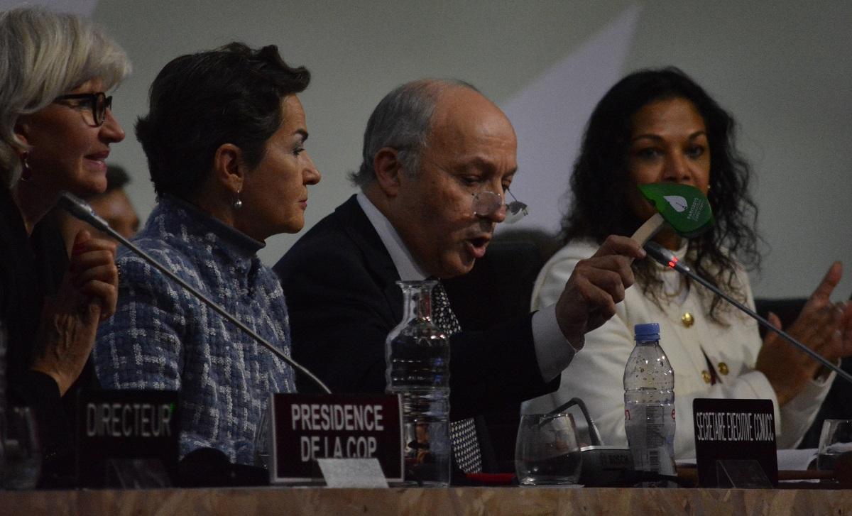 写真・図版 : 木づちを打って「パリ協定」の採択を宣言するCOP21議長のファビウス仏外相(当時。右から2人目)=2015年12月13日、パリ