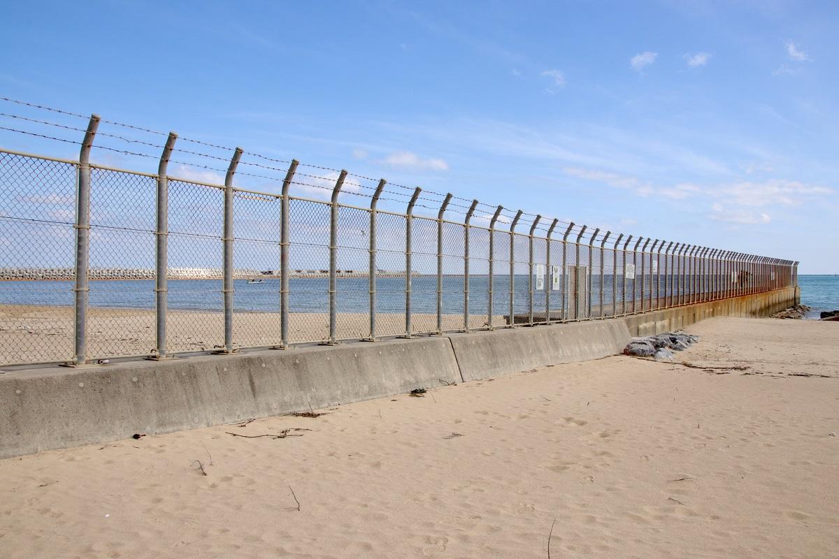 写真・図版 : 辺野古の浜を区切るフェンス。この先は米軍に提供された区域(筆者撮影)