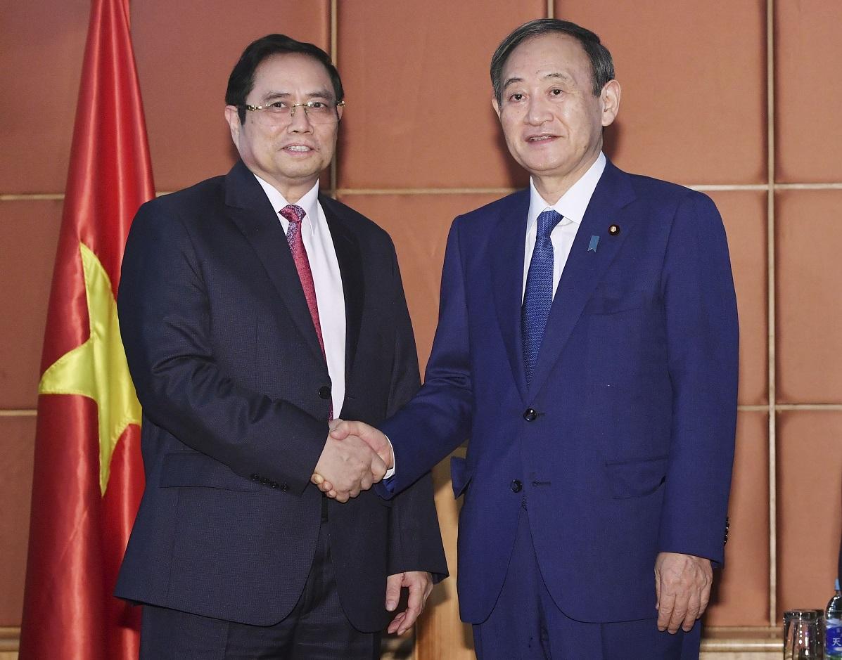 写真・図版 : ベトナム共産党のチン党中央組織委員長(左)と握手を交わす菅義偉首相=2020年10月19日、ハノイ