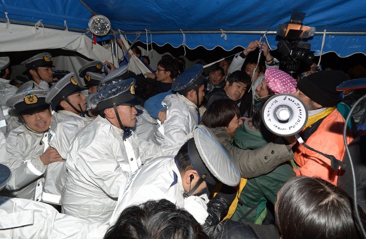 写真・図版 : 震災がれき受け入れの市民説明会の会場前で押し合う、反対派の市民と警察官ら=2012年11月13日、大阪市此花区