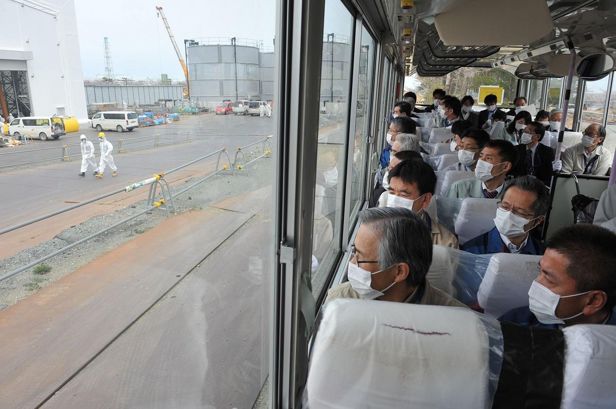 写真・図版 : バスの車内から福島第一原発構内を視察する住民ら=2014年4月18日