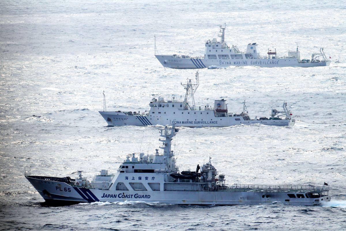 写真・図版 : 2013年、尖閣諸島付近の日本領海を航行する中国海洋監視船(奥の2隻)を警戒し併走する海上保安庁の巡視船(手前)=朝日新聞社機