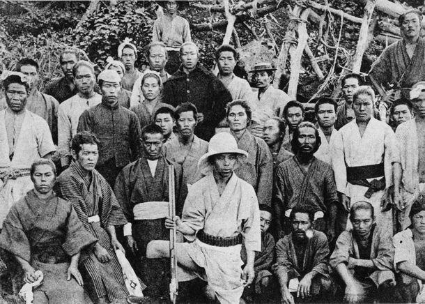 明治時代の尖閣列島。島民と共に記念写真に収まる猟銃を手にした古賀辰四郎さん=古賀花子さん提供