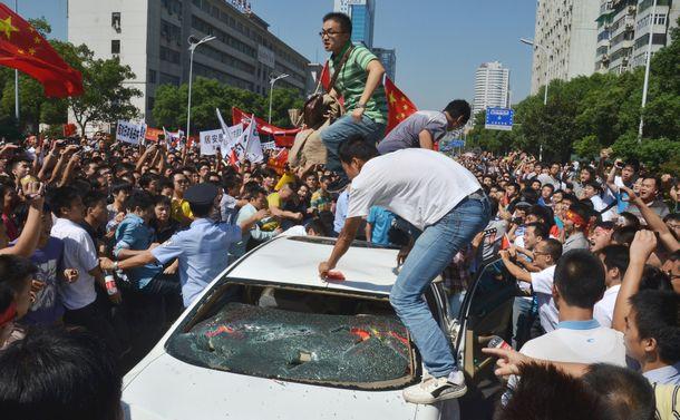 写真・図版 : 暴徒化し、日本車を破壊するデモ隊の一部。運転手は中国人だった=2012年9月15日、中国・湖南省長沙