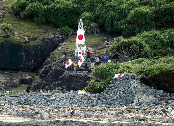 写真・図版 : 尖閣諸島の魚釣島に上陸し、日の丸を振る人たち=2012年8月19日、沖縄県石垣市