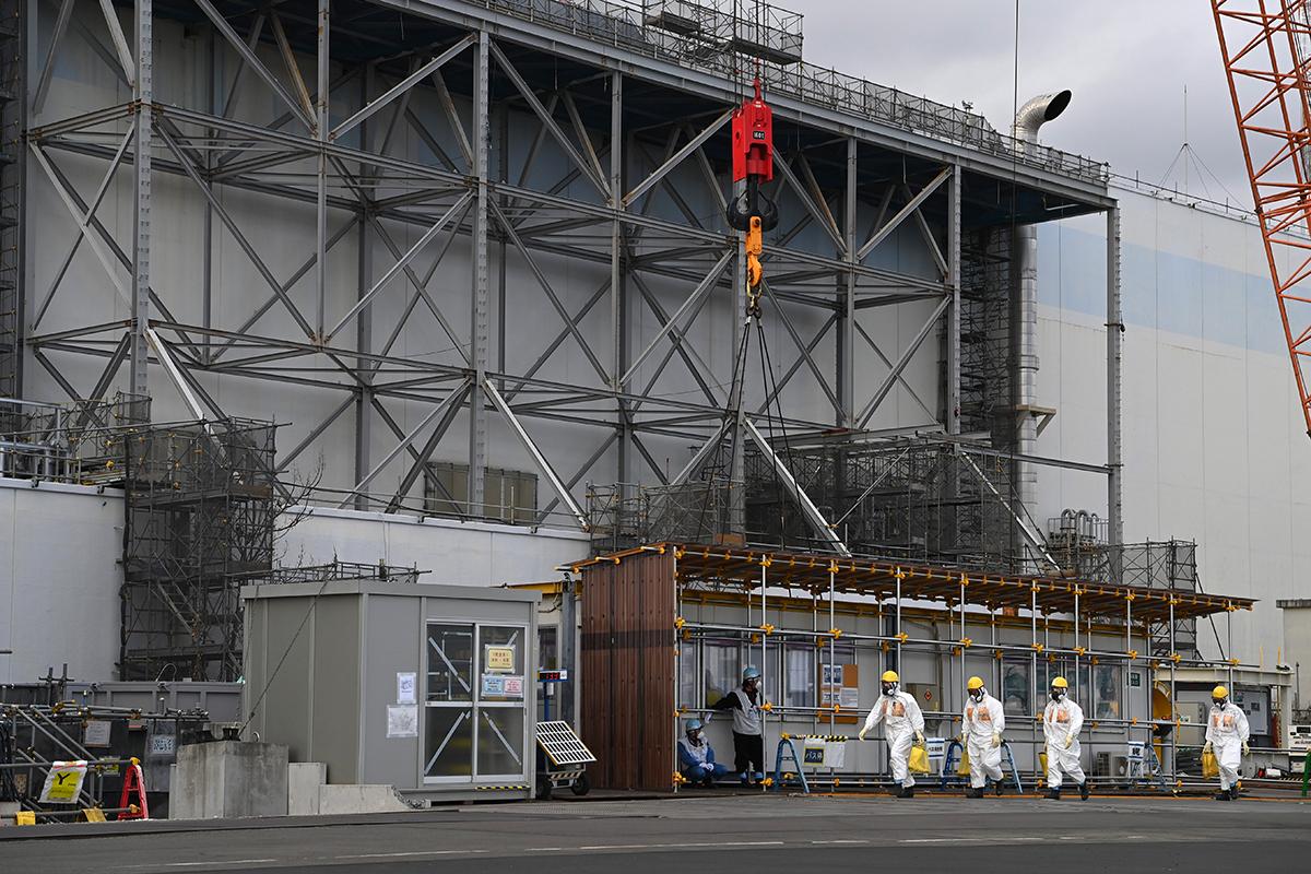 写真・図版 : 3、4号機タービン建屋と海の間を歩く作業員たち=2021年2月1日午後、福島県大熊町