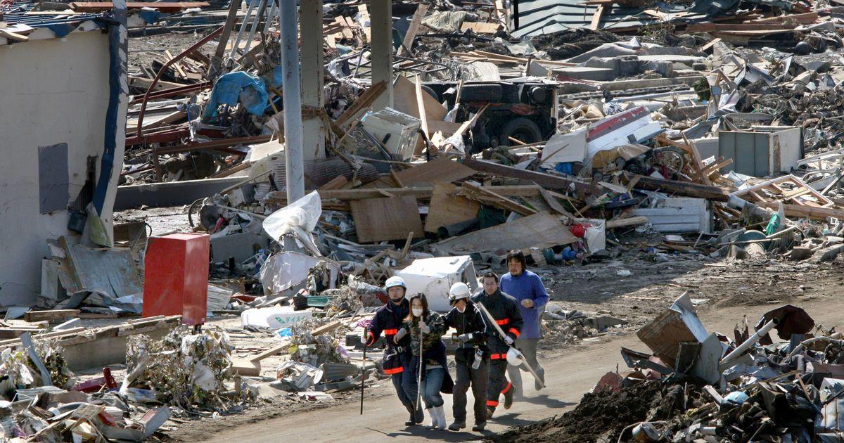 写真・図版 : 津波の被害を受けた宮城県石巻市の鮎川浜地区。「津波警報」との情報で手助けを受けながら女性が高台を目指していた=2011年3月14日