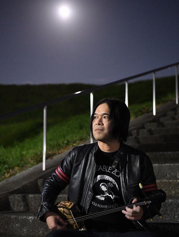 写真・図版 : 満月を背にして、三線(さんしん)を弾くロックバンド「ソウル・フラワー・ユニオン」の中川敬(たかし)さん=2020年12月29日、大阪府内