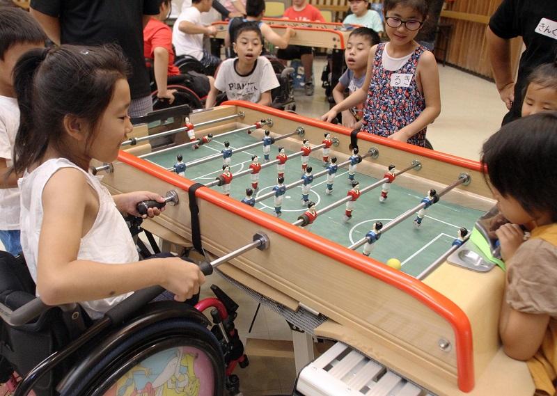 写真・図版 : テーブルサッカーの体験会でゲームに夢中になる障害児たち=2017年7月9日、高崎市寺尾町