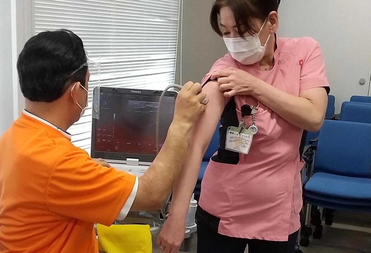 写真・図版 : 皮下脂肪の厚さを測る超音波検査を受ける宇治徳洲会病院の職員=京都府宇治市