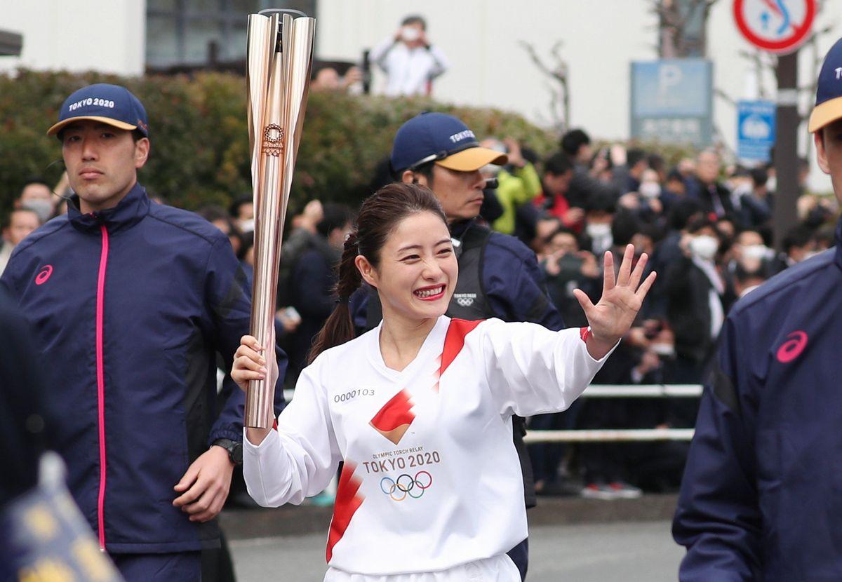 写真・図版 : 東京五輪の聖火リレーは3月25日に始まる予定だ。写真は昨年の聖火リレーのリハーサルでトーチをもって走る俳優の石原さとみさん=2020年2月15日、東京都羽村市