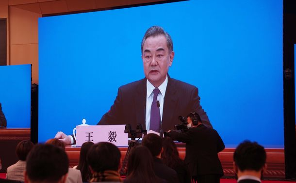 写真・図版 : オンライン形式で記者会見に臨む中国の王毅国務委員兼外相=2021年3月7日、北京
