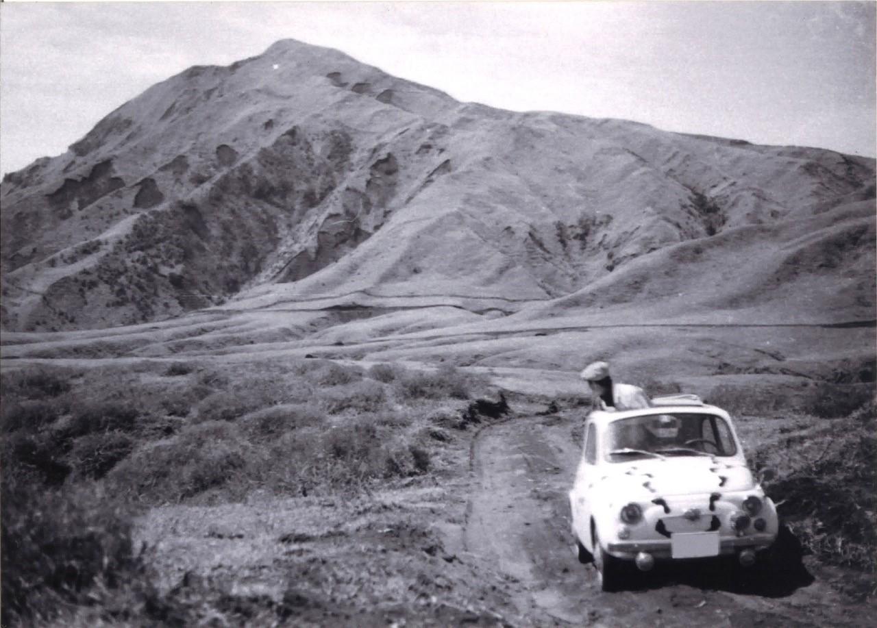 写真・図版 : 阿蘇の麓を立ったままFIAT500を運転する大塚康生さん。ヒッチハイカーに撮影を依頼したもの=1960年代末頃、ご家族提供