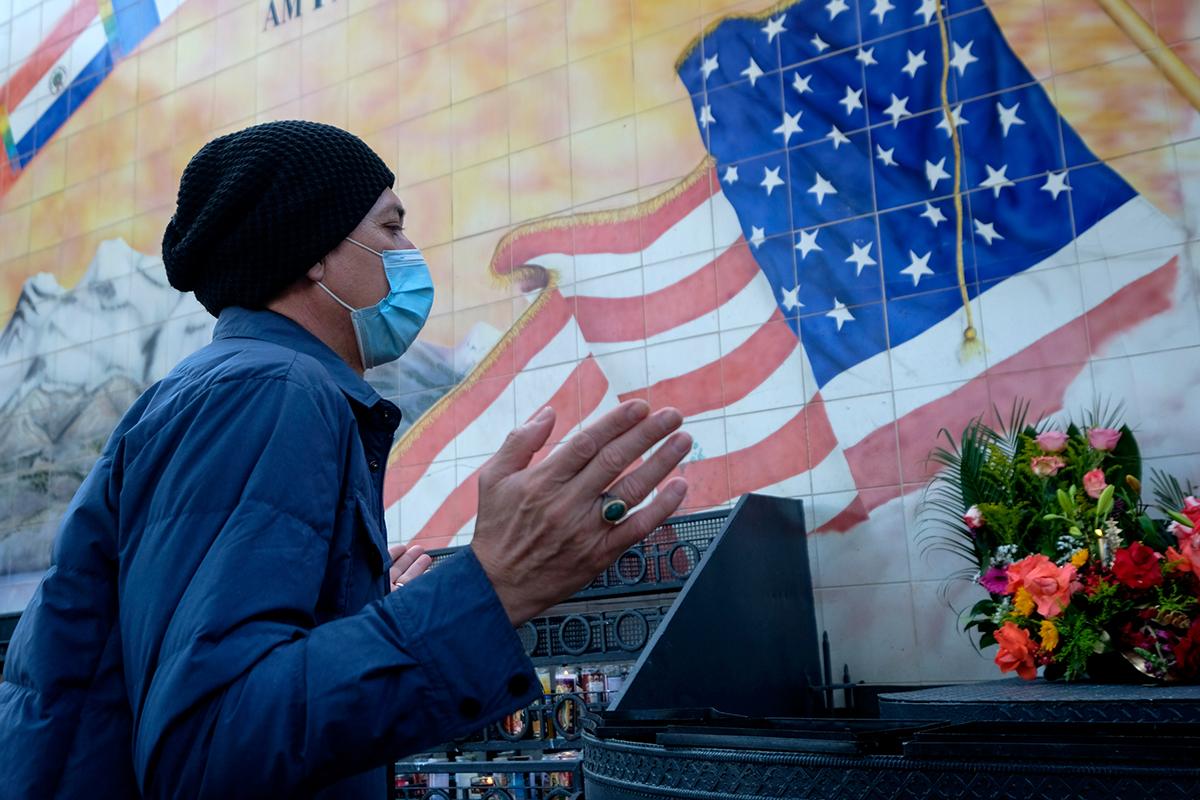 写真・図版 : 礼拝堂前で祈りを捧げるフェイスマスク姿の男性=2020年11月26日、米ロサンゼルス/shutterstock