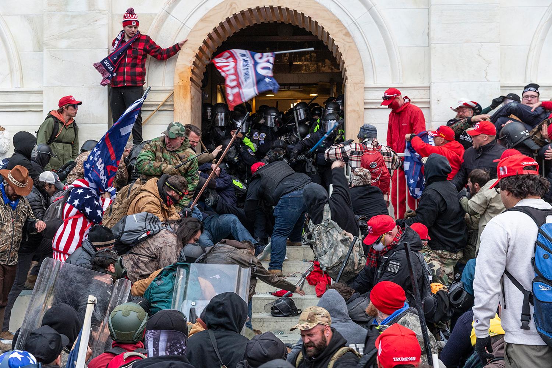 写真・図版 : 警察と衝突する国会議事堂の乱入者=2021年1月6日、米ワシントン/shutterstock