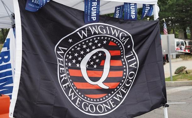 写真・図版 : トランプ氏の選挙集会の会場周辺で掲げられていたQアノンの旗=2020年9月26日、米ペンシルベニア州ミドルタウン