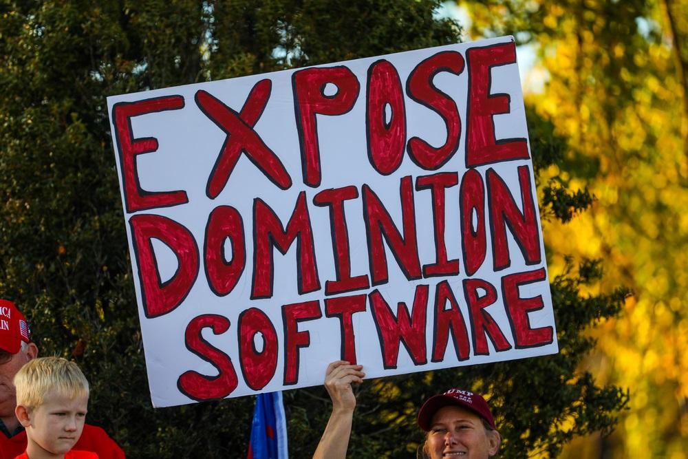 写真・図版 : 大統領選挙の開票後、「ドミニオン社のソフトの正体を暴け」と書いたプラカードをかかげるトランプ支持者=2020年11月14日、ワシントン Nicole Glass Photography / Shutterstock.com