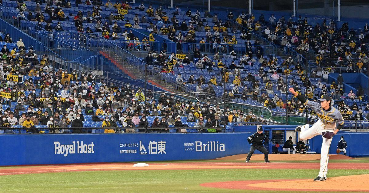 写真・図版 : プロ野球開幕戦を迎えた神宮球場。阪神・ヤクルト戦のスタンドはマスクをした観客が間隔を空けて座っていた=2021年3月26日、神宮球場