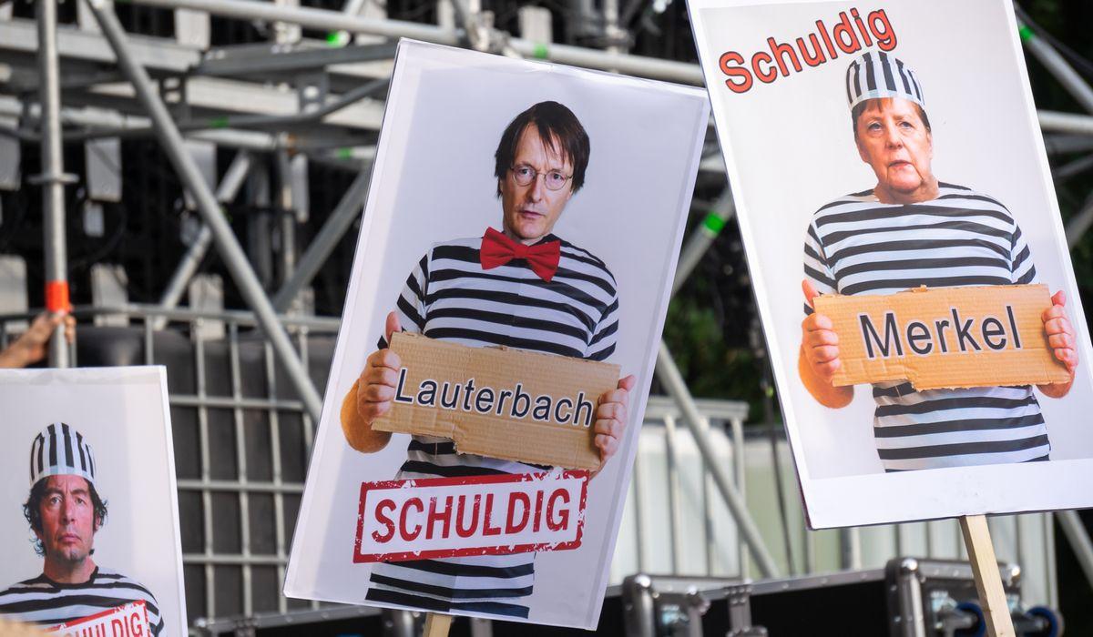 写真・図版 : 政府のコロナ対策に抗議するベルリンでのデモでは、メルケル首相らを囚人に模して「有罪」と記したボードが掲げられていた=Jaz_Online/Shutterstock.com
