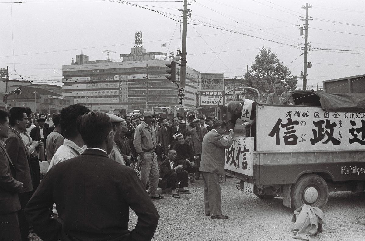 写真・図版 : 戦後衆議院議員となった辻政信は、のち参議院全国区に鞍替えして立候補。当時の新聞紙面では「あちこちで旧部下が現れ、辻候補と固い握手」と伝えられている=1959年5月、大阪市