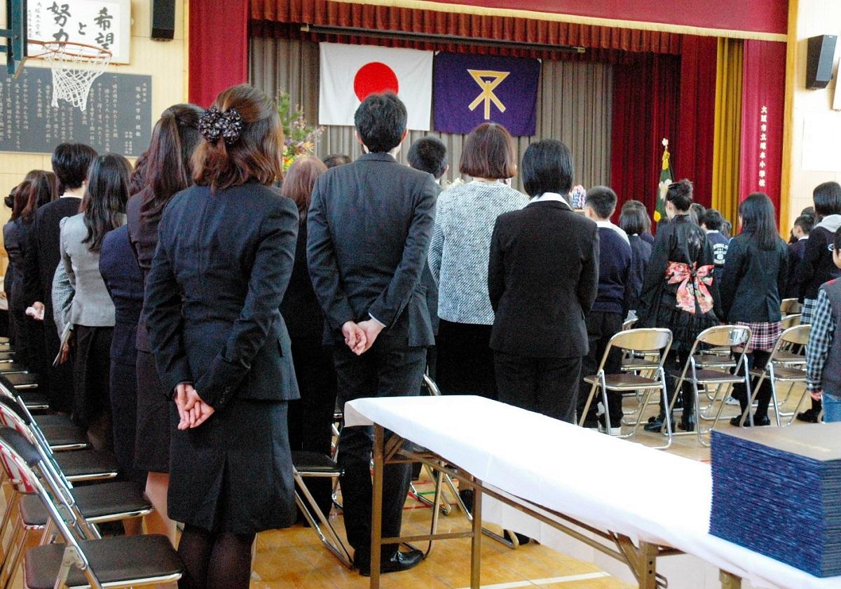 写真・図版 : 卒業式で君が代を起立斉唱する大阪市立小学校の教職員。大阪市では2011年、「自治体教職員は学校行事で行う国歌斉唱は起立により斉唱する」とした〝君が代条例〟が制定された=2012年3月21日