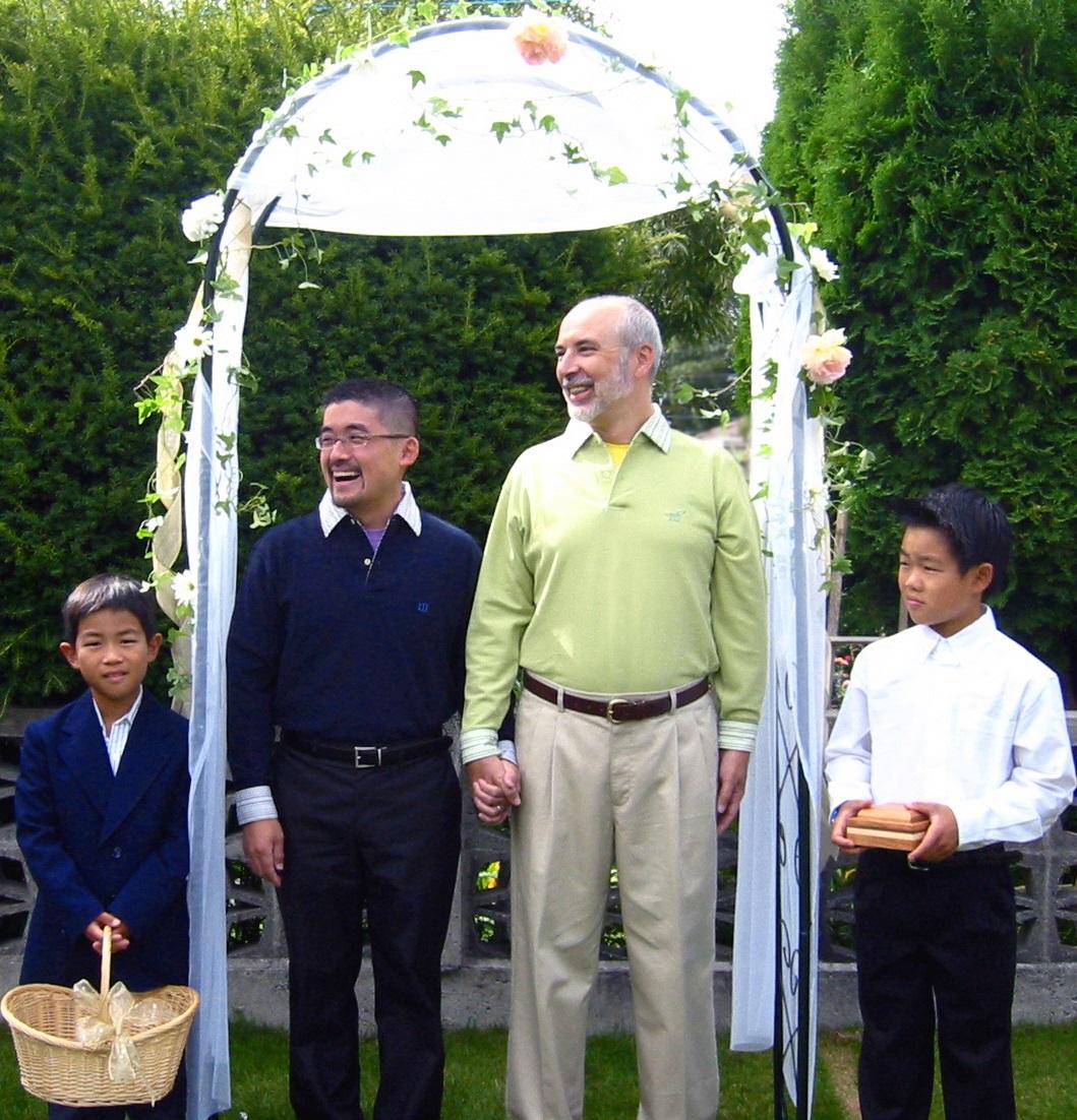 写真・図版 : 幼い甥っ子たちに祝福されて、手作りのウェディングアーチをくぐる筆者(左から2番目)とパートナー。結婚式のスタイルも自由で様々=2004年9月 筆者提供