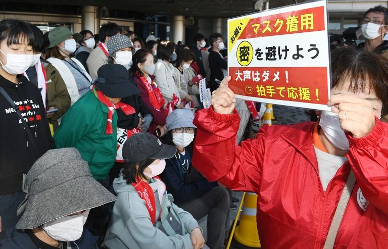写真・図版 : 聖火ランナーが走る場所では、「密を避けよう」とプラカードを示す係員の姿も=2021年4月7日、三重県津市北河路町