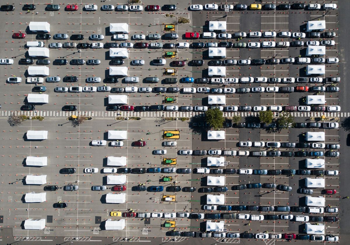 写真・図版 : カルフォルニア州立大学ロサンゼルス校の駐車場を利用した大規模なワクチン接種会場。住民たちは車で列をなして順番を待っている=2021年2月17日(Ringo Chiu/Shutterstock.com)