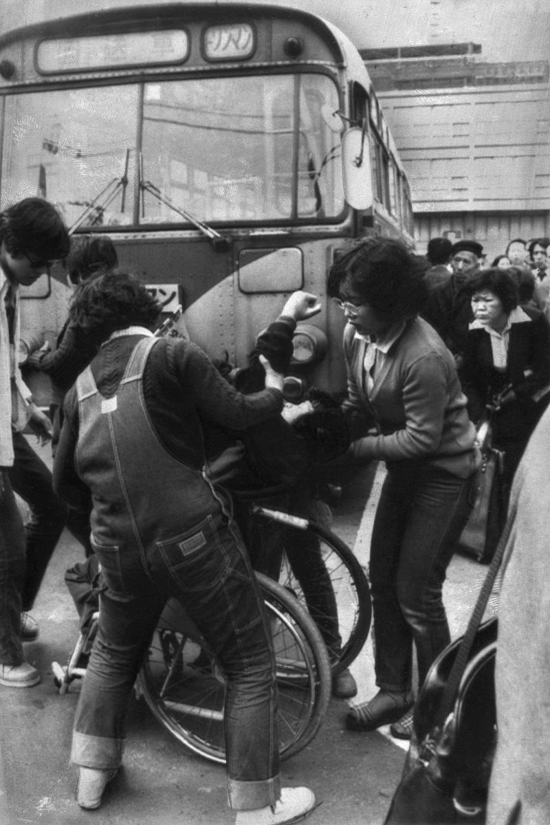 写真・図版 : 車椅子に乗った数十人の脳性マヒの人たちが、介護人に車椅子ごと抱えられバスに乗り込んだ。車椅子への乗車拒否が相次いだことに対する抗議行動として取り組まれ、「川崎バス闘争」として大きく報道された=1977年4月12日、神奈川県川崎市