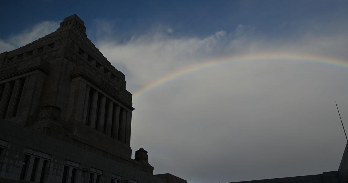 写真・図版 : 背後の空に虹が架かった国会議事堂=2021年2月15日