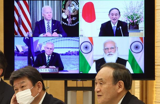 写真・図版 : オンラインで会談する日米豪印の首脳。手前右は菅義偉首相。画面内は(右下から時計回りに)モディ印首相、モリソン豪首相、バイデン米大統領=2021年3月12日、首相官邸