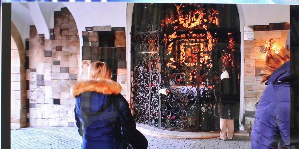 """写真・図版 : 石の門内部に飾られた""""奇跡の絵""""と親しまれているマリア像に祈る市民=筆者撮影"""