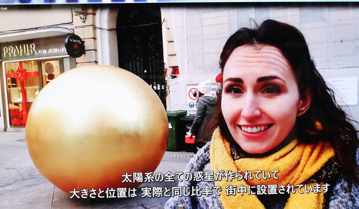 写真・図版 : 歩道に設置された金色に輝く太陽の彫刻作品。水星、金星、地球などはこの周辺のビルの壁に飾られている。日本語の字幕つきでガイドを受けられた=筆者撮影